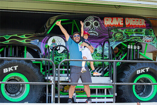 An excited father hoists his son up for a happy photo opportunity in front of the full-scale Gravedigger Monster Truck at RC Fest 2019.