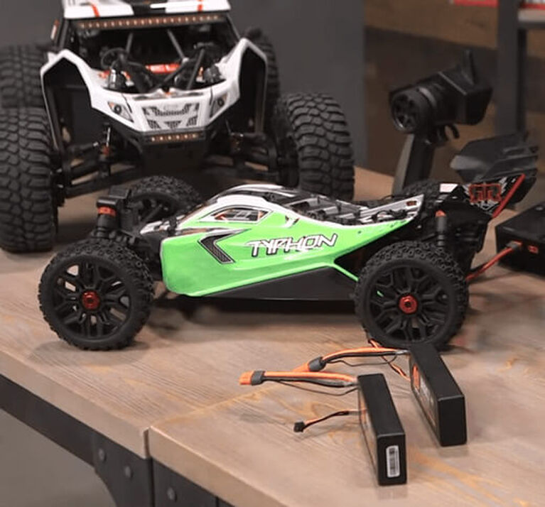 A couple of RC surface vehicles, charger and transmitter sitting on a workbench.