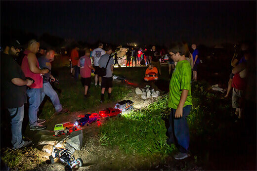 RC rock racers drive their trucks through a nighttime course at RC Fest 2019.