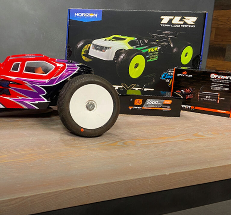 A TLR 8IGHT E-Truggy Kit and Accessories on a bench.