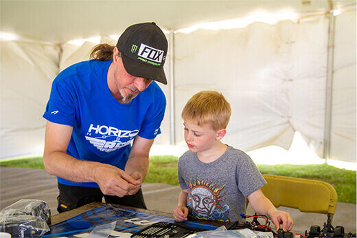 Andrew Warren works on an ECX vehicle with an interested AMP Camp participant  at RC Fest 2019.