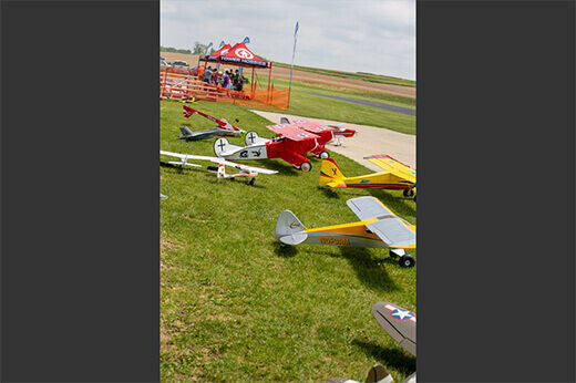 High-wing RC planes align the runway near a Tower Hobbies pop-up tent at RC Fest 2019.