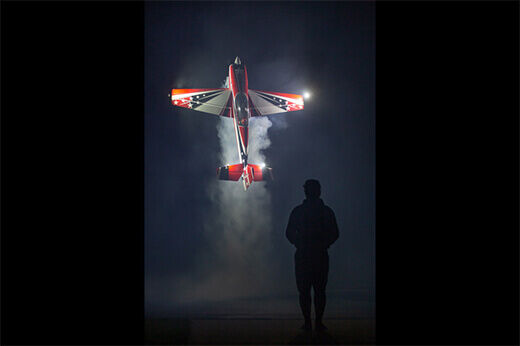Jase Dussia hovers his smoking stunt plane in a night exhibition at RC Fest 2019.