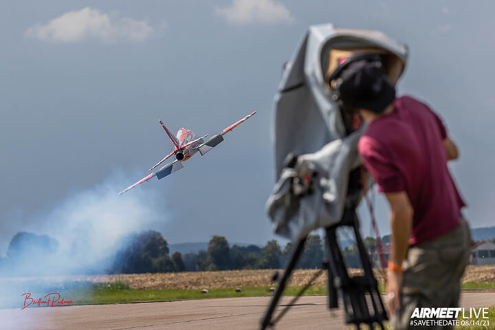 A video cameraman records an rc plane taking off from the runway
