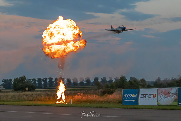 An RC warbird buzzed the runway over a small firework explosion.